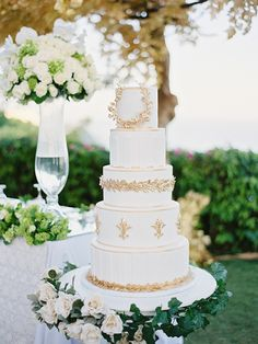 White tiered wedding cake with gold Grecian-inspired details {Facebook and Instagram: The Wedding Scoop}