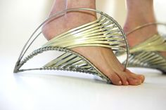 """Naomi Hertz's Bridge Shoe   Naomi Hertz's Bridge Shoe Infatuated with the way the bridges by architect Santiago Calatrava """"challenge their very connection to the ground,"""" Hertz used tension to reinvent the way a shoe carries the body. For all its artistry and intellectual merit, pressing strips of icy metal into the soles and intimately acquainting your toes with the ground illustrates the painful disconnect between theory and practice."""