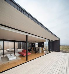 A #minimalist single-storey house in Chile by Nuform overlooks the ocean and features a #pine #wood #terrace where lying down