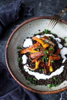 Sweet and Spicy Roasted Moroccan Carrots over Spiced lentils with yogurt - a simple, delicious and hearty vegetarian meal. | www.feastingathom...