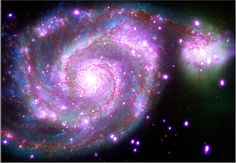 """This galaxy, nicknamed the """"Whirlpool,"""" is a spiral galaxy, like our Milky Way, located about 30 million light years from Earth. This composite image combines data collected at X-ray wavelengths by Chandra (purple), ultraviolet by the Galaxy Evolution Explorer (GALEX, blue); visible light by Hubble (green), and infrared by Spitzer (red).  Read the full article at: http://www.visiontimes.com/2015/01/25/2015-international-year-of-light-is-upon-us.html?photo=2"""