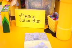 """Kids' table...bubbles, Contact paper chalkboard placemats, chalk, custom coloring books, homemade heart and arrow shaped crayons, boxes of fresh Craolas, pinwheels in lieu of flowers, a stainless steel cold drink container filled with iced juices and chocolate milk.  Topped off with a hand painted """"DJ's Milk & Juice Bar"""" sign (DJ is the groom's son and the adorable ring bearer."""