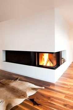 Schlichter geht's kaum - und denoch ist dieser BRUNNER Eckkamin ein Highlight, das selbst einen großen, kühlen Raum mit Atmosphäre und Wärme versorgt. Ein Boden aus Nussbaumholz, eine schwarze Feuerraumverlängerung und sehr üppige weiße Wände ergänzen das Bild zu einem wunderschönen Ganzen.