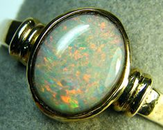 SUNSET FLASH BLACK CRYSTAL OPAL 14K RING SIZE 11 SCA141127  Origin:SOLID BLACK CRYSTAL OPAL FROM LIGHTNING RIDGE AUSTRALIA  OPAL SIZE - 10 X 7.5 MM  RING SIZE - 11  MULTI FLASH COLOUR; BEAUTIFUL SUNSET ORANGE AND GREEN SHIMMER FLASHES