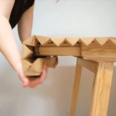 Wooden Cloth table by Nathalie Dackelid | This table by design student Nathalie Dackelid can be extended by folding out a series of batons that hang beside the legs.