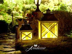 Dwa białe drewniane lampiony nocą w ogrodzie. Two white wooden lanterns in the garden at night.