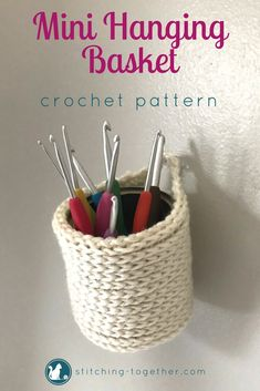 Adorable crochet mini hanging baskets you can make with this free crochet pattern. Perfect to hold crocht hooks, pen, brushes or fold it down to hold keys or tape! The mini baskets can be hung on the wall or placed on a desk. Imagine how cute they would look in your office! #crochet #crochetbasket #freepatterns #crochetpattern #crocheting #stitchingtog #freecrochetpattern #minibasket #diy