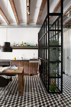 Tone down the modern, make a little more rustic industrial with black white checkered floors, industrial warehouse windows for the room divider, and make the cabinets a bit more barn woody, and for god's sake get rid of those awful modern chairs and light