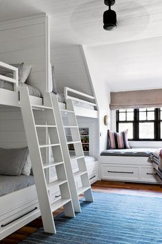 Beach style boys bedroom boasts a blue rug leading to white ladders mounted on side by side built-in bunk beds accented with shiplap trim as well as black and white striped bedding.