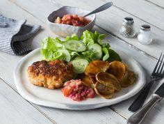 Zalmburgers met gebakken aardappelen, salade en rabarbercompote Een burger gemaakt van gesnipperde zalm en verse kruiden