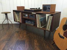 New mid century modern record player console, stereo cabinet with LP album storage featuring black walnut with tapered wood legs.