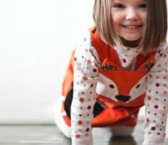 Girls and baby Fox dress. Mr Fox in socks has arrived on the scene,and hunting for adventure.Dress up for a party or wear every day! Available in girls dress sizes 6m to 8yrs Classic pinafore shape in orange European superior quality super soft 100% cotton needle corduroy.  Double button strap fastenings on inside of yoke,allows you to adjust hte dress as your little girls grows. Beautiful hand applique fox face on the front yoke, with little ears,and matching printed cotton edged paw p...
