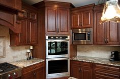 Corner double oven.  Cherry shaker cabinets. Staggered cabinetry design.