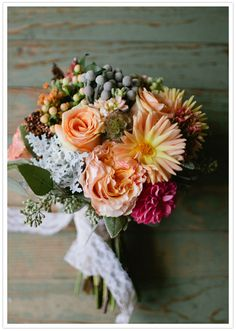 dusty miller, lamb's ear, variegated pittosporum, camellia, seeded eucalyptus, coral hypericum berries, silver brunia berries, globe scabiosa, ruffled garden roses, blush pink ranunculus, milva roses, soft peach tea roses, orange wax flower, and a yellow spiky dahlia bouquet
