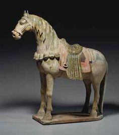 A RARE OLIVE-GLAZED AND PAINTED RED POTTERY FIGURE OF A CAPARISONED HORSE  SUI/EARLY TANG DYNASTY, 6TH-7TH CENTURY