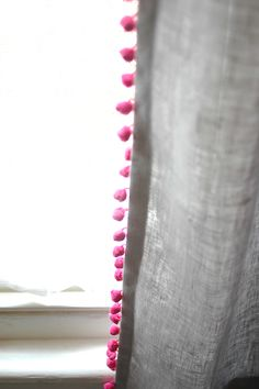 Add a bright contrasting (or white) pom pom trim to curtains to jazz them up.