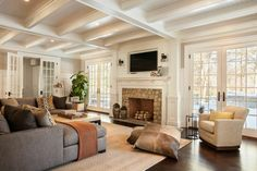 The home's great room has coffered ceilings and a large stone hearth fireplace with a white mantle and an inset television. The room is filled with soft, comfortable furniture, including two enormous pillows for lounging on the floor. On either side of the great room are French doors that lead out onto the patio.