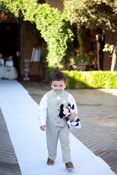 Ring bear in a gray suit and bow tie walking down the aisle of the outdoor wedding ceremony carrying bride Minnie Mouse and groom Mickey Mouse | Brie Marie Photography| villasiena.cc
