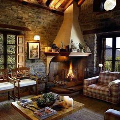 Corner fireplace, stone walls, plank floors and casement windows in a casual living room / family room