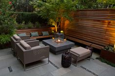 small courtyard garden with concrete fire feature and horizontal slat wood fence