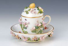 Cover cup and saucer, Meissen, circa 1880, all-round rich applied bell flowers and on theunderside of saucer, to this slightly worn, fine colorful painting of floral arrangement and insects, gold decoration