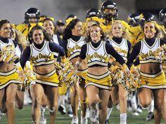 Cheerleaders Lead the Football Team on the Field