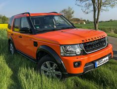 facelifted orange Land Rover Discovery with black wheel arches