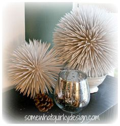 Toothpicks + spray paint + floral foam ball make these crazy looking snowballs for hanging or displaying. They would also work great spray painted a different color for a coastal cottage feel adorning a book shelf.