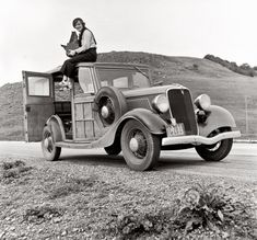 Dorothea Lange, Resettlement Administration photographer, in California atop car with her giant camera. February 1936.