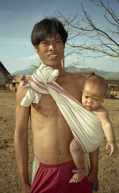 Here's a proud father in Vietnam doing Daddy duty, most likely while multitasking and doing his manual labor at the same time (ie. working in the the rice fields).