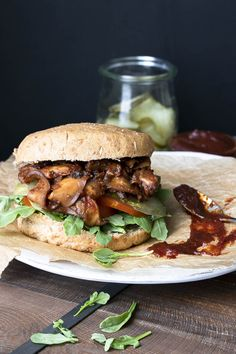 Vegan pulled pork sandwich with mushrooms topped with arugula, pickles and tomatoes
