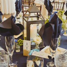 Blue reception decor; Rustic lanterns paired with small vases of white flowers topped reception tables along with champagne flutes stuffed with elegant blue napkins.