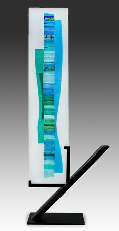 Aqua Blue Waterfall by Alicia Kelemen. Textured blue and aqua glass is fused to a white panel, supported by a black steel base. Each piece is unique and will vary slightly. Glass panel is 18
