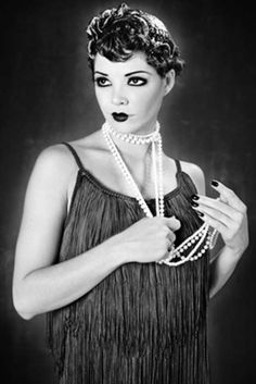 A Chanel Flapper dress, short boyish hair style, dramatic make up and pouting lips - all typical of 1920s fashion.