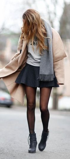 Beige coat over black mini skirt with gray tee and scarf.