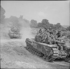 British Churchill tanks carrying infantry advance towards St Pierre Tarentaine, Normandy, 3 August 1944.