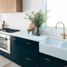 Silestone Blanco Orion countertops matched with classic navy cabinetry http://www.CabinetsAndDesigns.net/Products/Silestone/