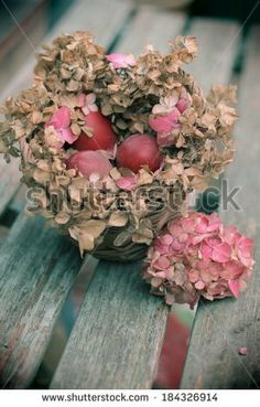 Instagram - esque image of a floral pink and brown hydrangea nest of dyed red eggs on a wooden bench, vintage Easter,  - stock photo
