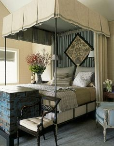 """The master bedroom is exceptionally large and high-ceilinged, so its gunmetal canopy bed from Hollyhock creates """"a room within a room."""""""