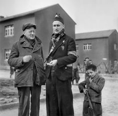 "Just liberated Buchenwald concentration camp inmates enjoy a smoke in the company of a young boy obviously ready to play ""war"" with his toy rifle. All three belong to the lucky ones. April 1945."