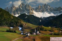 Santa Maddalena, Trentino-Alto Adige, Itália.View of the picturesque church of St. Magdalena in the Val di Funes, Italy. The hills are covered in yellow dandelions and those jagged peaks in the background are the Dolomites
