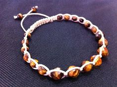Shamballa Tiger Eye Bracelet $10.00  Beautiful Unisex Shamballa Tiger Eye Bracelet.  It is really a great looking bracelet and it looks wonderful in men and woman. This particular bracelet is 8 inches fully close and it goes to 11 inches fully open. On this bracelet I'm using a Swarovski Crystal, 8mm, faceted, rondelle, topaz color as a focal. The cord that I'm using here is handcraft waxed cotton cord, natural color.    Tiger Eye Attributes: Emotional Clarity