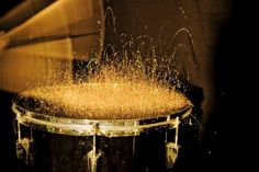 Drum sticks hitting a drum covered with gold glitter..