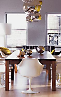 Grouping of silver pendants over dining table (tulip chairs!)