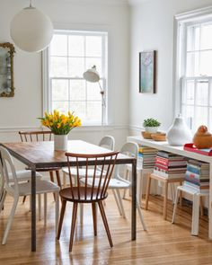 There's a reason why Scandinavian homes use a lot of white - it makes the long winters easier to endure when you're in a light-filled space. The white walls, chairs, and accessories in this dining area feel anything but stark when surrounded by stacks of books and a fresh floral centerpiece | domino.com