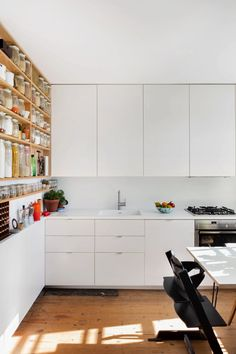 White Ikea kitchen cabinets with Corian countertops in London apartment