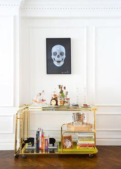 Feminine, gold bar cart with not-so-feminine skull art above home bar