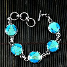 @Overstock.com - Handcrafted Mexican Alpaca Silver and Turquoise Disk Bracelet (Mexico) - Handcrafted by women in a cooperative in Mexico, this alpaca silver link bracelet is comprised of five round handcast pieces inlaid with a mosaic of turquoise.  The bracelet measures 8.5 inches in length.   http://www.overstock.com/Worldstock-Fair-Trade/Handcrafted-Mexican-Alpaca-Silver-and-Turquoise-Disk-Bracelet-Mexico/7568954/product.html?CID=214117 $31.99