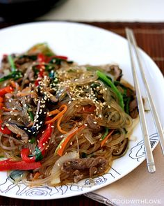 "Japchae, a rather popular dish served at Korean restaurants. Japchae is a dish of stir-fried glass noodles (called ""dangmyeon""), containing vegetables like carrots, red peppers, onions and scallions, and is usually seasoned with soy sauce, sugar and sesame oil."