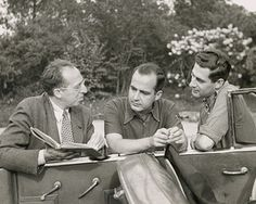 Aaron Copland, Samuel Barber and Gian-Carlo Menotti looking at a book next to a convertible.